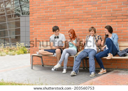 Students friends hanging out sitting on bench outside university campus - stock photo