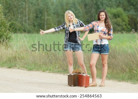 Students girls hitchhiking with an empty cardboard - stock photo