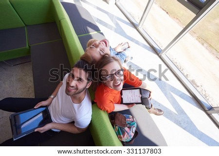 students group working on school  project  together on tablet computer  at modern university - stock photo