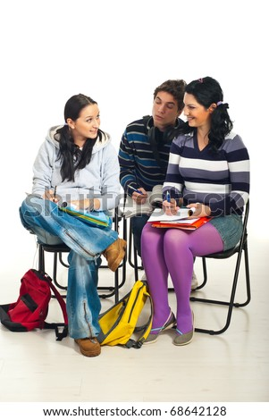 Students having a conversation and sitting on chairs in a classroom - stock photo
