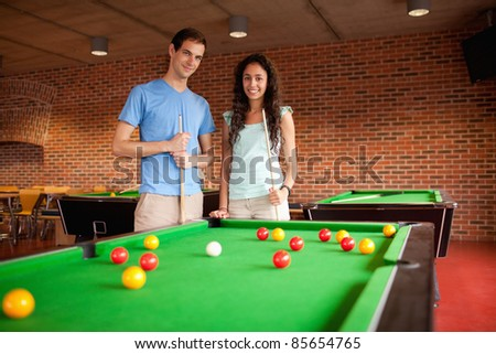 Students holding queues while standing next to a pool - stock photo