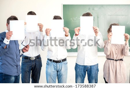 Students holding white blank papers for advertising - stock photo