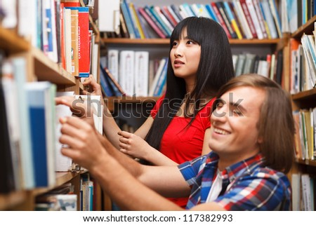Students in a library choosing a book - stock photo