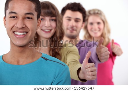 Students in a row giving the thumb up. - stock photo