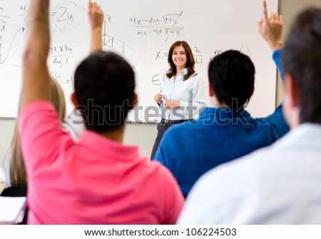 Students in class asking questions to the teacher - stock photo