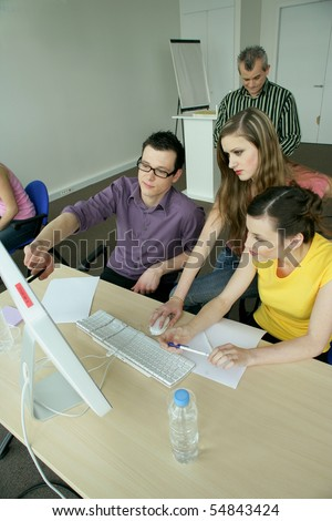 Students in front of a desktop computer - stock photo