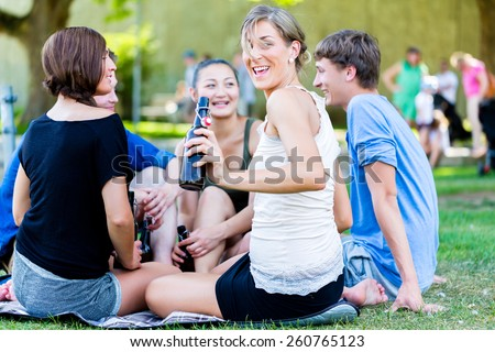 Students in park drinking beer and talk having picnic at river - stock photo