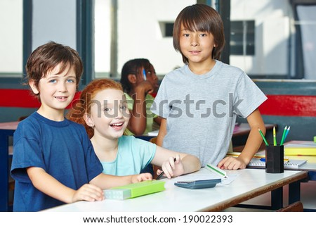 Students learning together in a group in elementary school class - stock photo