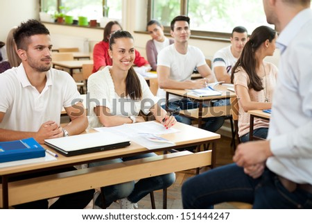 students listening to a university lecture with tutor  - stock photo