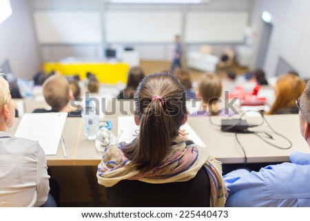 Students listening to lecture and making notes. Professor giving presentation in lecture hall at university.  - stock photo