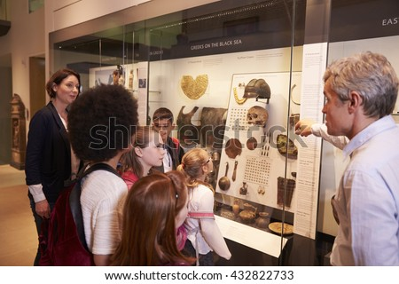 Students Looking At Artifacts In Case On Trip To Museum - stock photo