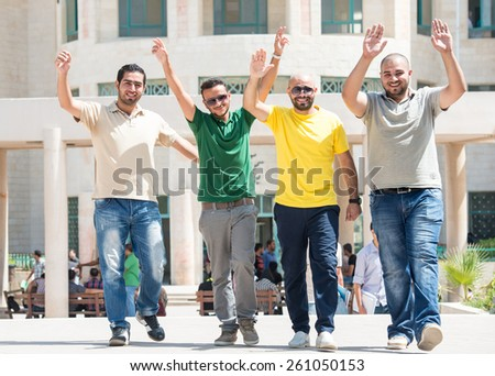 Students on university campus with rised hands - stock photo