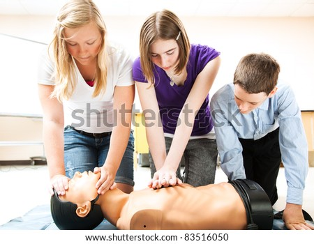 Students practicing CPR life saving techniques on a mannequin. - stock photo