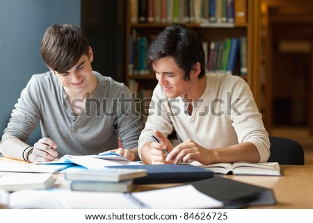 Students preparing an essay in the library - stock photo