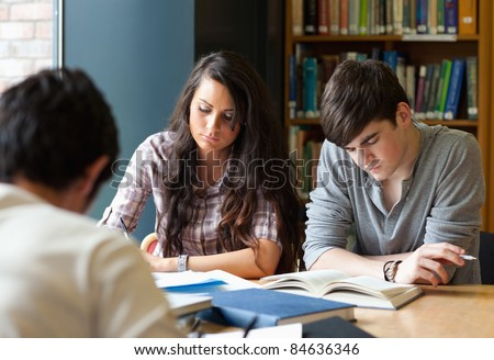Students preparing the examinations in a library - stock photo