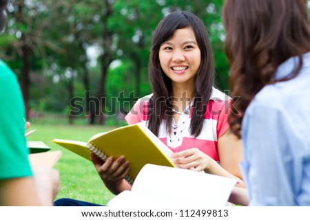 Students reading a book together in the park - stock photo