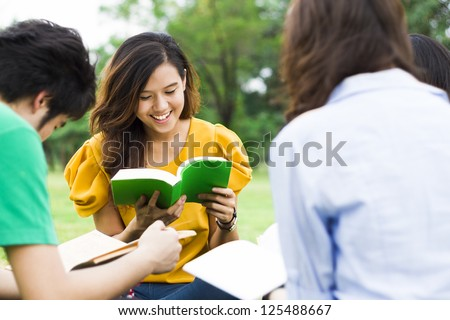 Students reading a book together in the park. - stock photo