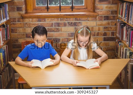 Students reading books while sitting down at the elementary school - stock photo