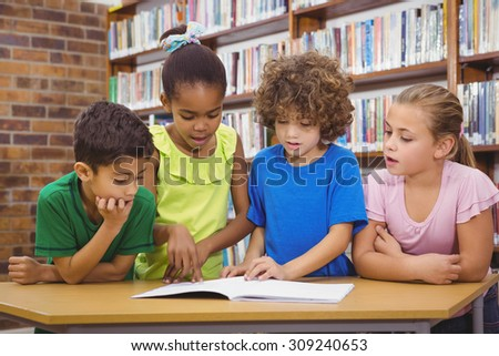 Students reading froma school book at the elementary school - stock photo