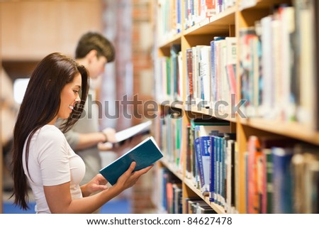 Students reading while standing up in a library - stock photo