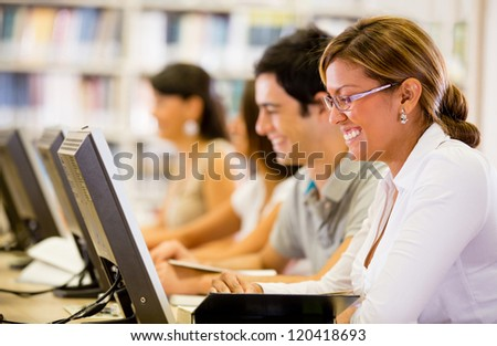 Students researching online at the library on computers - stock photo