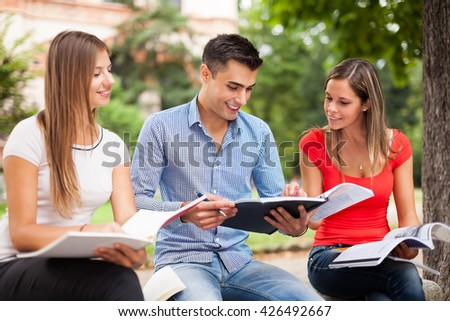 Students sharing their notes while sitting outdoors - stock photo