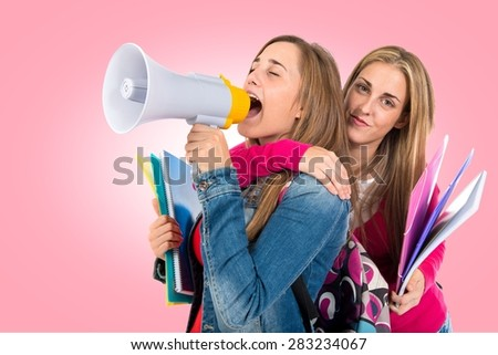 Students shouting by megaphone over colorful background - stock photo