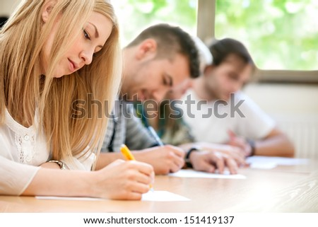 students sitting for an examination in an amphitheater - stock photo