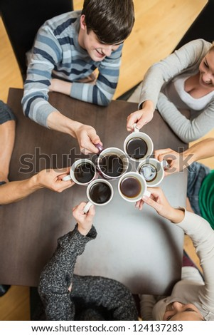 Students sitting holding cups of coffee smiling in college cafe - stock photo