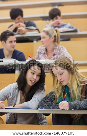 Students sitting in a lecture hall while studying while using a tablet pc and talking - stock photo