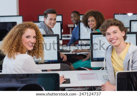 Students smiling at camera in computer class at the college - stock photo