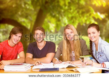 Students studying against trees and meadow in the park - stock photo