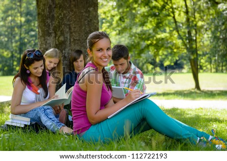 Students studying on meadow in park teens writing reading campus - stock photo