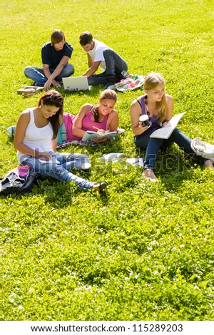 Students studying sitting in the park teens reading writing laptop - stock photo