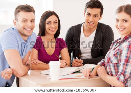 Students studying together. Four cheerful students studying sitting at the desk together and smiling at camera - stock photo