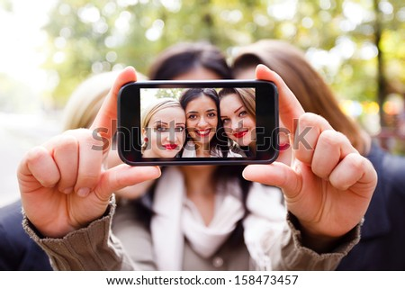 Students taking a self portrait with smart phone. - stock photo