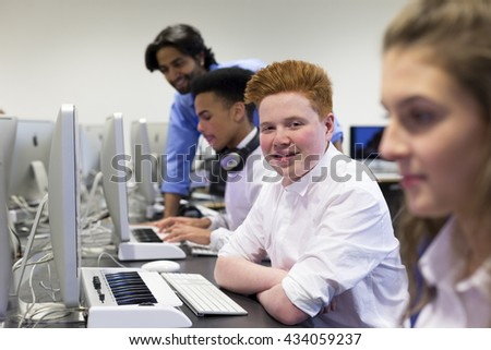 Students using computers in a school lesson. One student is smiling at the camera. There is a teacher helping another student in the background.  - stock photo