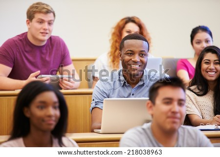 Students Using Laptops And Digital Tablets In Lecture - stock photo