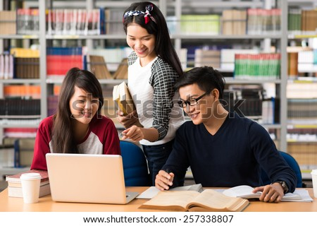 Students watching something on the laptop in library - stock photo