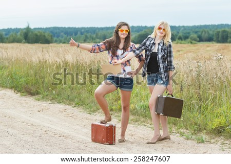 Students wearing sunglasses hitchhike on country road - stock photo