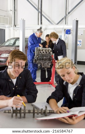 Students with auto part studying automotive trade in vocational school - stock photo