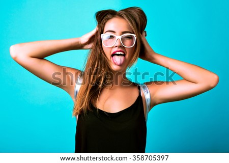 Studio bright crazy portrait of cheeky young woman screaming showing tongue and winking, blue background, black top, cheerful funny style, sportive tanned body, party fun. - stock photo