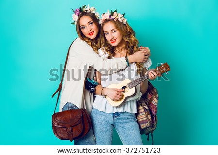 Studio closeup colorful portrait of  two young funny fashion girls  posing on blue wall background in summer style outfit with  flowers  wreath wearing blue jeans and boho bag pack. . - stock photo