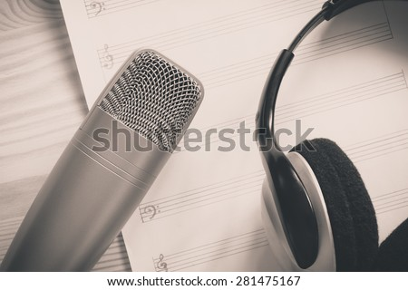 studio condenser microphone & headphone on blank music sheet, on wood / old black and white film processed for music concept background - stock photo