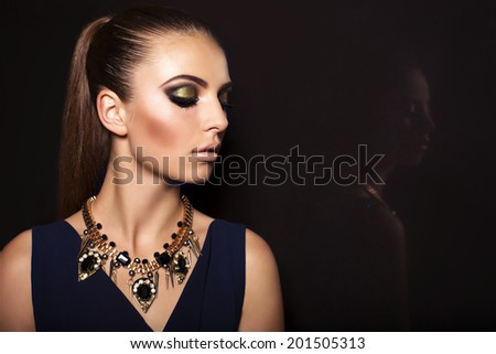 studio fashion portrait of beautiful glamour model with dark hair and luxury necklace - stock photo
