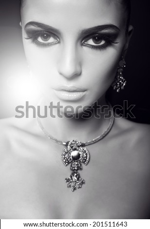 studio fashion portrait of beautiful glamour model with smokey eyes makeup and golden necklace - stock photo