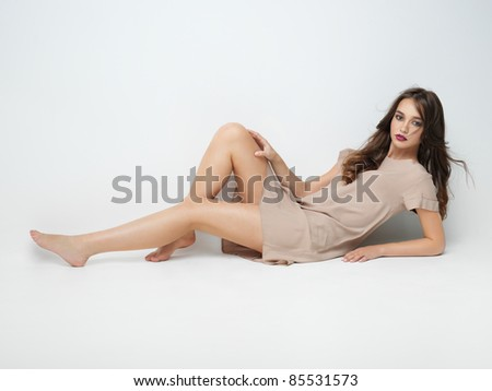 studio fashion portrait of beautiful young woman, sitting, on white background, posing at camera - stock photo