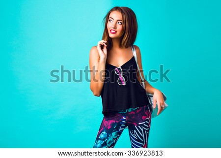 Studio fashion portrait of sexy hipster woman, tanned perfect skiing bright make up, trendy sportive outfit, printed leggings, silver backpack, student party look, mint blue background. - stock photo