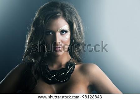 Studio fashion portrait with dark skin and golden makeup - stock photo