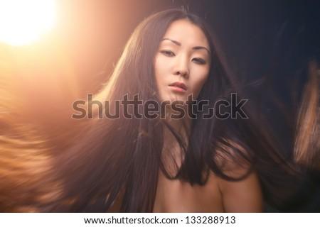 Studio fashion shot of asian woman on dark background - stock photo
